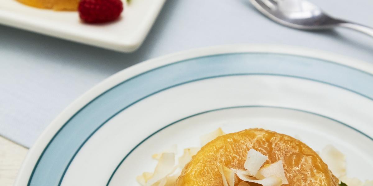 Foto de um prato azul com branco com um quindim dentro decorado com lascas de coco e morangos