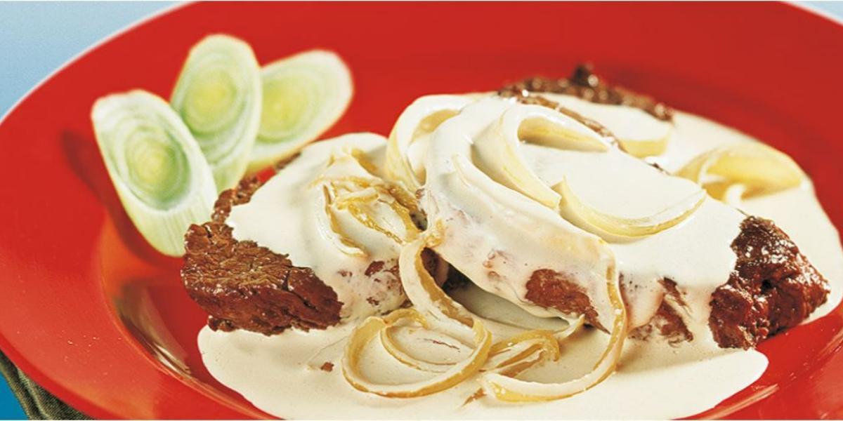 foto tirada de uma prato redondo e vermelho com dois bifes, creme por cima e cebolas