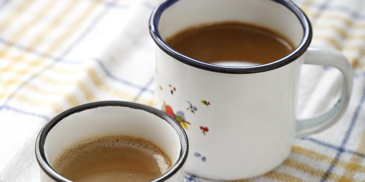 Fotografia em tons de branco, bege e azul, com duas canecas brancas com borda azul contendo bebida em tons café-com-leite, sobre guardanapo branco com listras azul e bege, tudo sobre bancada de madeira.