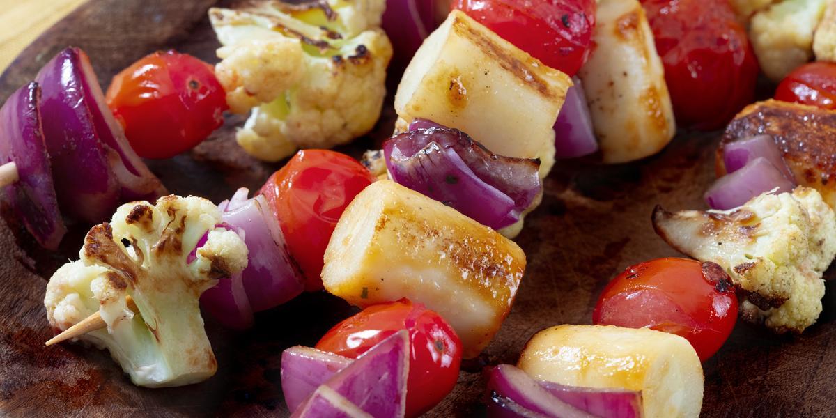 Fotografia em tons de cinza de um prato redondo cinza escuro com quatro espetinhos de legumes.