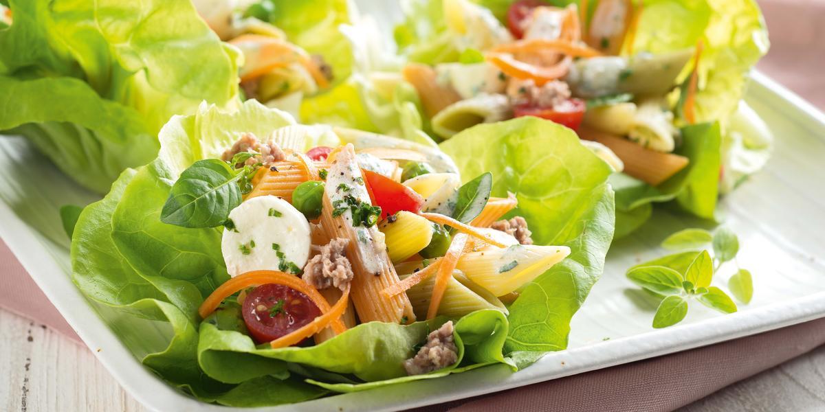Fotografia em tons de branco e verde, ao centro salada de folhas verdes com macarrão, legumes e mozarela, sobre guardanapo rosa e bancada de madeira em tons de branco.