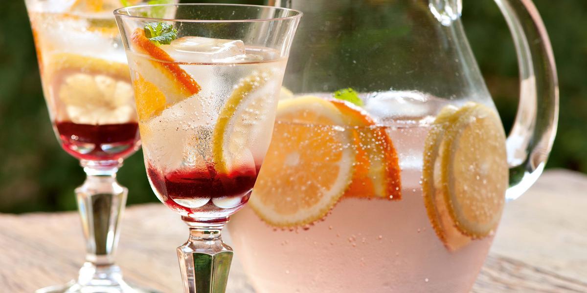 Fotografia em tons de rosa em uma bancada de madeira clara com uma jarra de vidro com o refresco de hibisco e frutas cítricas dentro, decorando com rodelas de laranja. Ao lado, duas taças de vidro com o refresco.