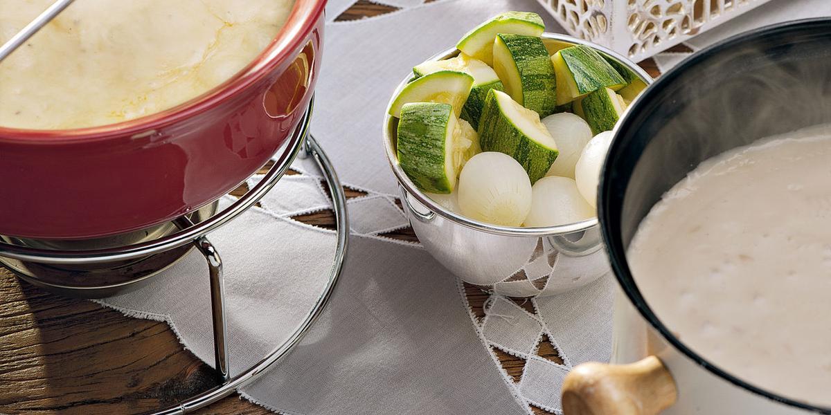 recipientes nas cores vermelho e branco ambos comporta o fondue de queijo, outros recipientes estão com os acompanhamentos para o fondue como pão, presunto entre outros.