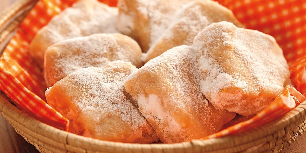 Fotografia em tons de laranja em uma bancada de madeira escura com uma cesta de vime com guardanapo laranja de bolinhas com algumas palhas italianas feitas com tangerina dentro dela.