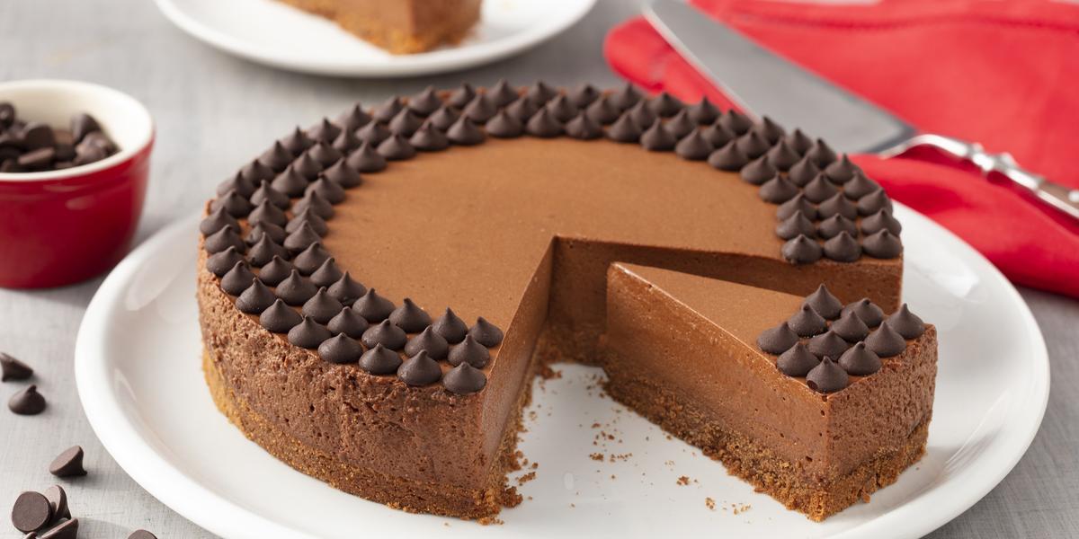Fotografia em tons de branco e vermelho de uma bancada branca com um prato branco, sobre ele uma torta de chocolate. Ao lado um paninho vermelho com uma espátula. Ao fundo um prato branco com uma fatia de torta e um potinho com gotas de chocolate.