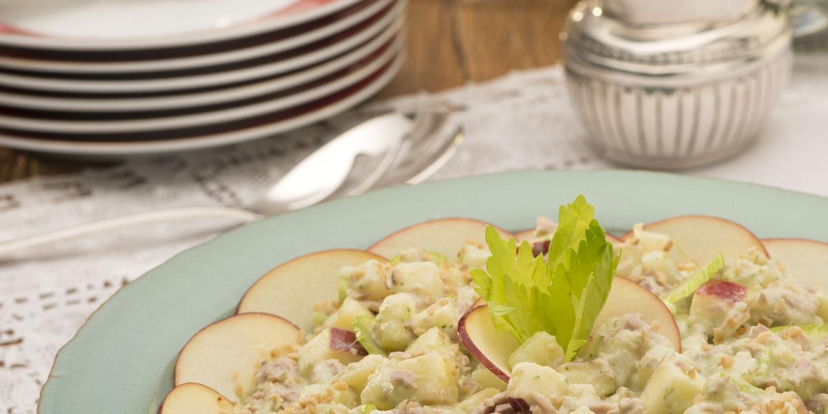 Em uma bancada marrom de madeira contém um pano branco, e um prato redondo azul claro com atum, pedaços de maçã e queijo. Ao fundo pratos empilhados nas cores branco e vermelho e duas taças transparentes