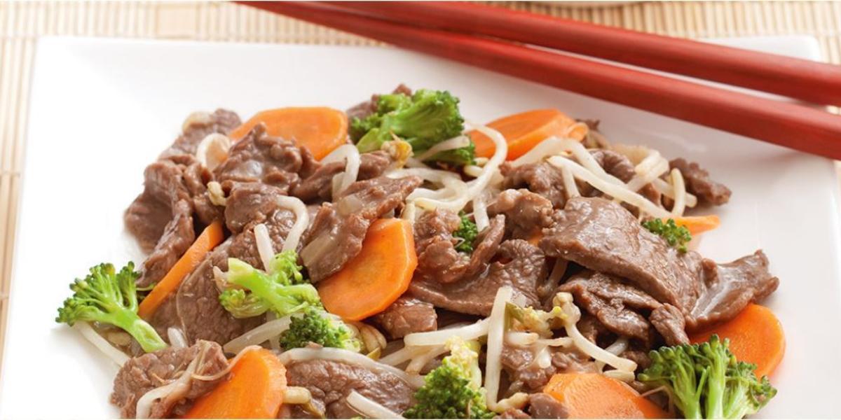 foto tirada de um prato quadrado branco com pedaços de carne, cenoura e brócolis