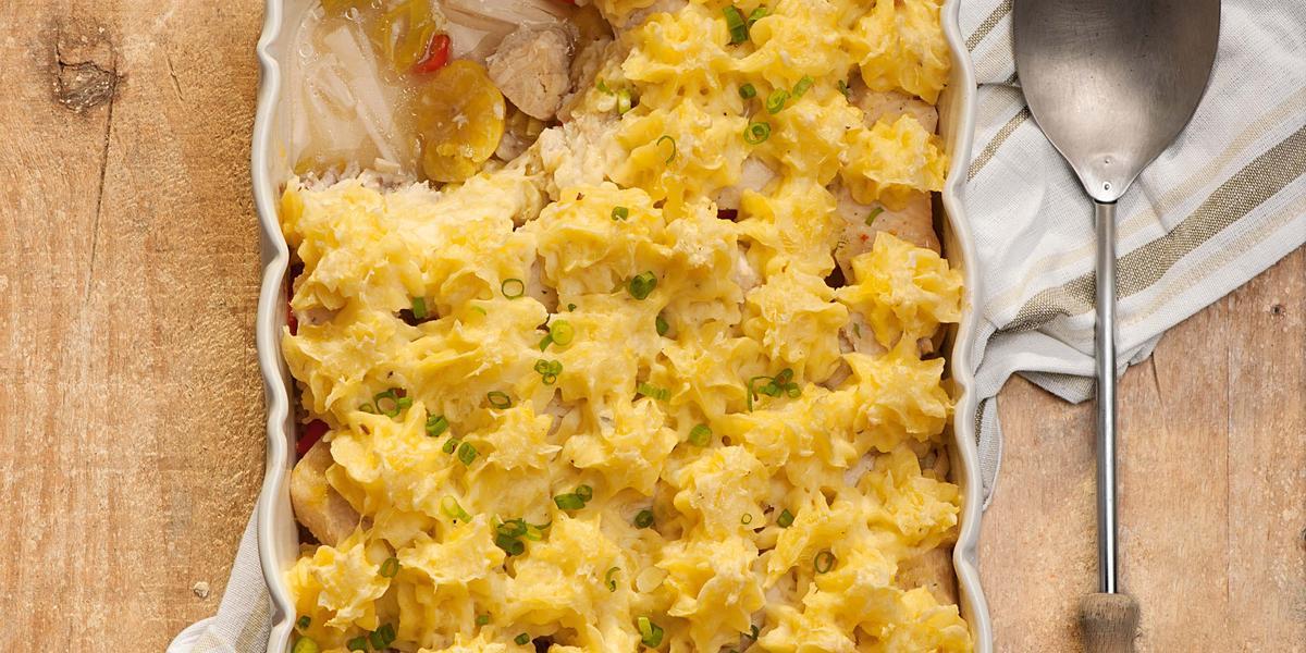 Fotografia em tons de amarelo em uma bancada de madeira clara com um refratário retangular e o peixe com purê de mandioquinha dentro dele. Ao lado, uma colher de servir e um pano branco com detalhes bege.