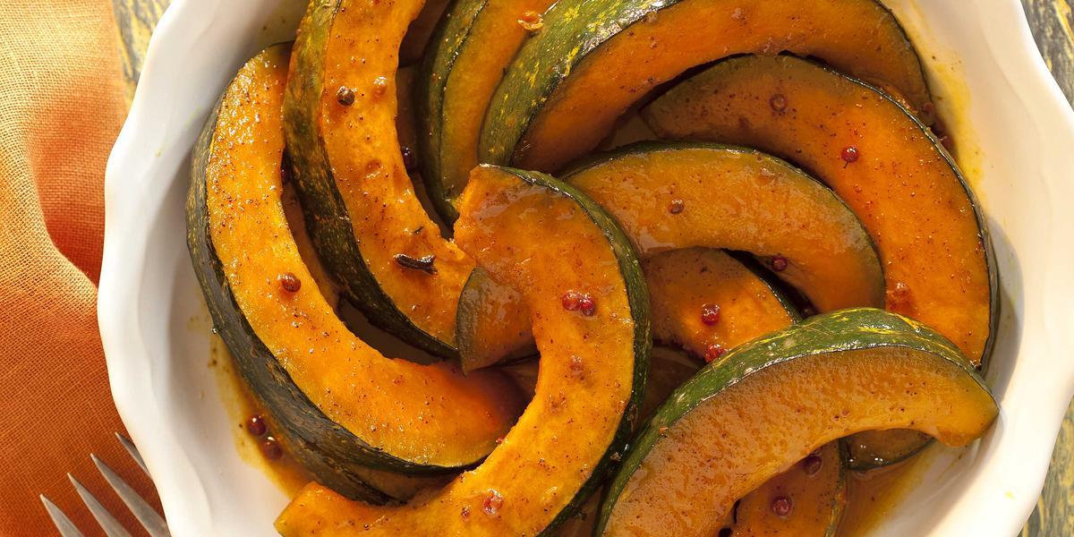 Fotografia em tons de laranja em uma bancada de madeira, ao lado um garfo apoiado em um guardanapo laranja e ao centro uma travessa redonda branca com as abóboras caramelizadas dentro.
