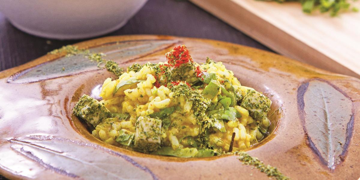 Foto de uma bancada com um prato de pedra fundo com a receita de Risoto de Azedinha. Além dele, há uma tábua com cubos de azedinha, um pote branco com verdura, uma garrafa com pimenta e uma faca