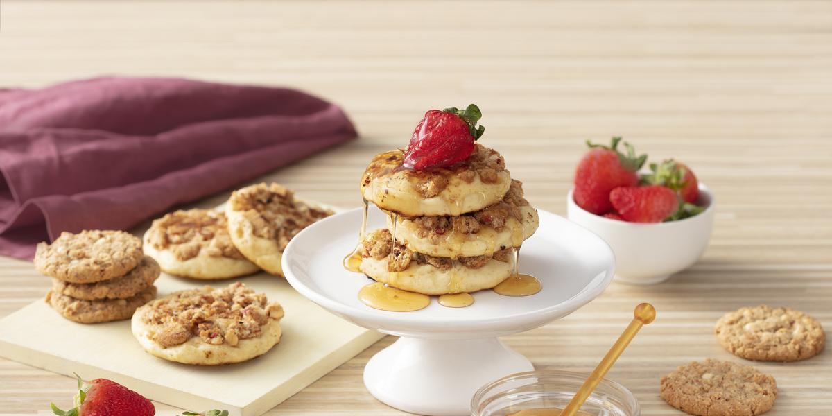 Foto de uma bancada de madeira clara. Sobre ela há morangos soltos e em um pote, cookies em uma tábua, um pote de vidro com mel e um guardanapo vinho. Ao centro há um prato com três pancakes cobertas com mel e decoradas com morangos.