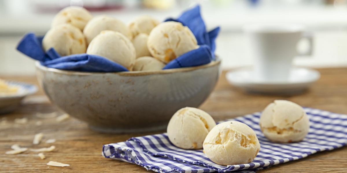 Foto de uma mesa com um pano e 3 pães de queijo redondos em cima. No fundo da foto há uma tigela com mais pães dentro