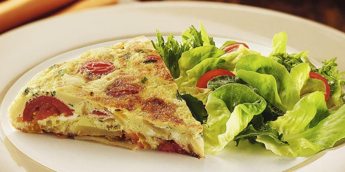 Fotografia em tons de verde em uma bancada com um prato branco redondo raso, um pano amarelo de fundo e a tortilla de omelete com batata e tomate em cima dele, ao lado, salada de alface e tomate cereja.