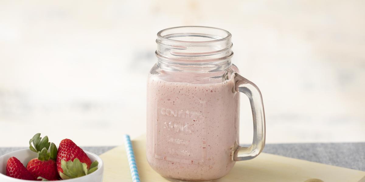 Fotografia em tons de azul e rosa de uma bancada, com uma tábua de corte, um copo com alça e a bebida de morango dentro. Ao lado um potinho com morangos.