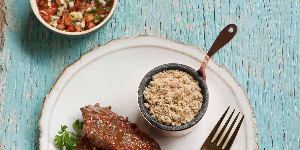 Fotografia em tons de azul e branco de uma bancada azul, sobre ela um prato branco com um bife, um garfo e um recipiente com farofa. Ao fundo um recipiente com vinagrete.