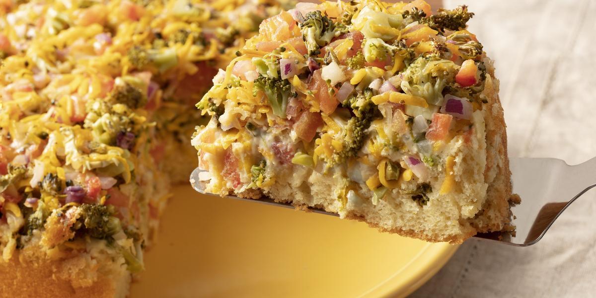 Fotografia em tons de amarelo e branco de um prato amarelo com a torta de legumes e uma espátula retirando uma fatia. Ao lado um paninho branco.