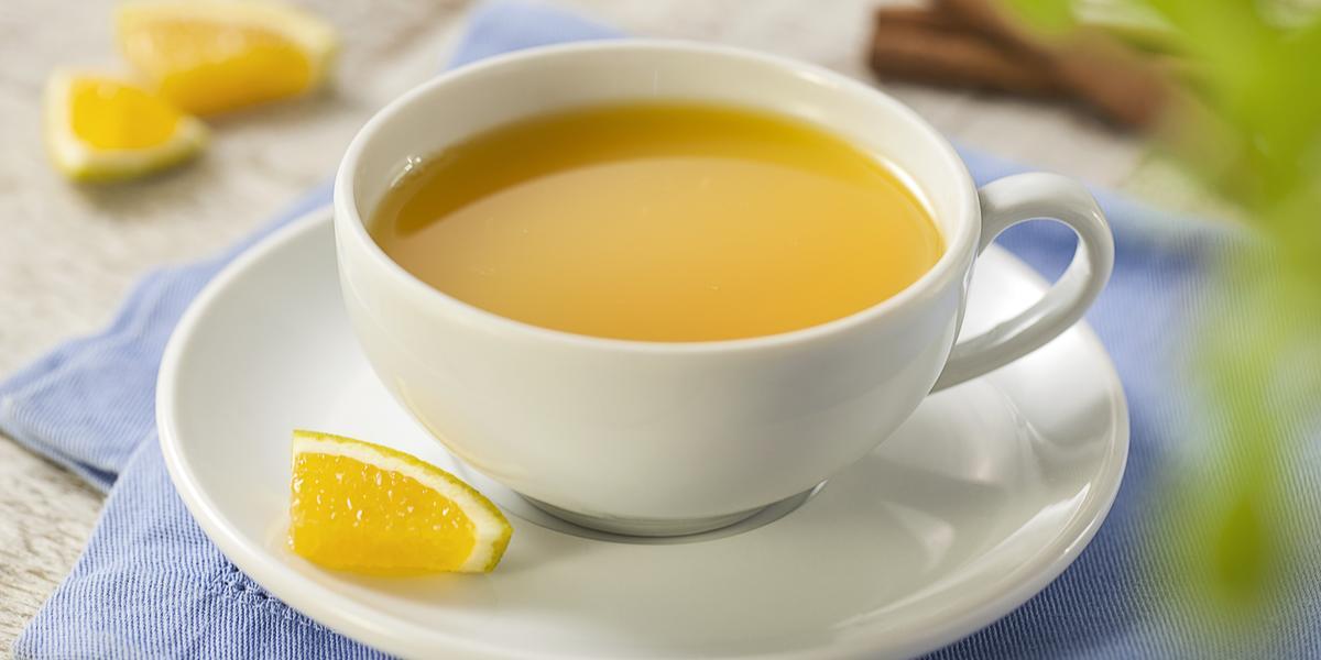 Fotografia em tons de azul, cinza e amarelo de uma bancada cinza com um paninho azul e sobre ele um prato branco redondo com uma xícara com chá de laranja. Ao fundo paus de canela e pedaços de laranja.