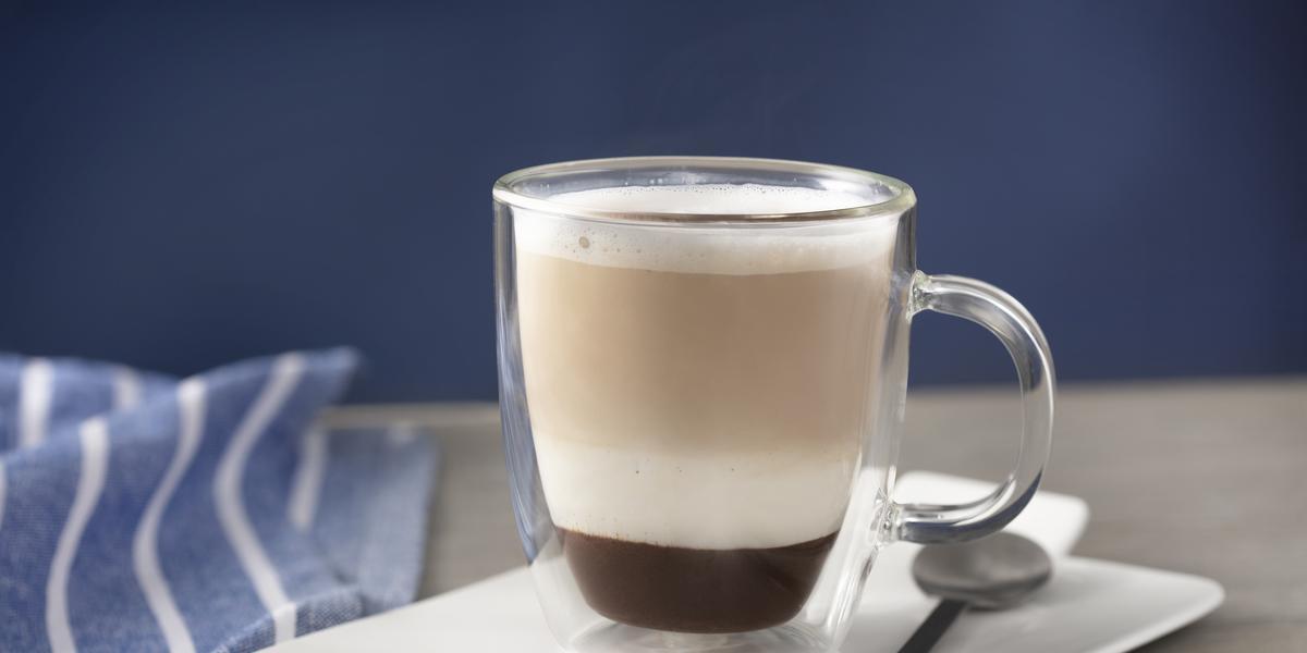 Foto de uma bancada cinza. Sobre ela há um prato branco quadrado com uma xícara de vidro com a bebida preparada dentro. A bebida tem uma camada marrom escura, uma branca e uma marrom clara. No prato há uma colher e do seu lado esquerdo um tecido azul.
