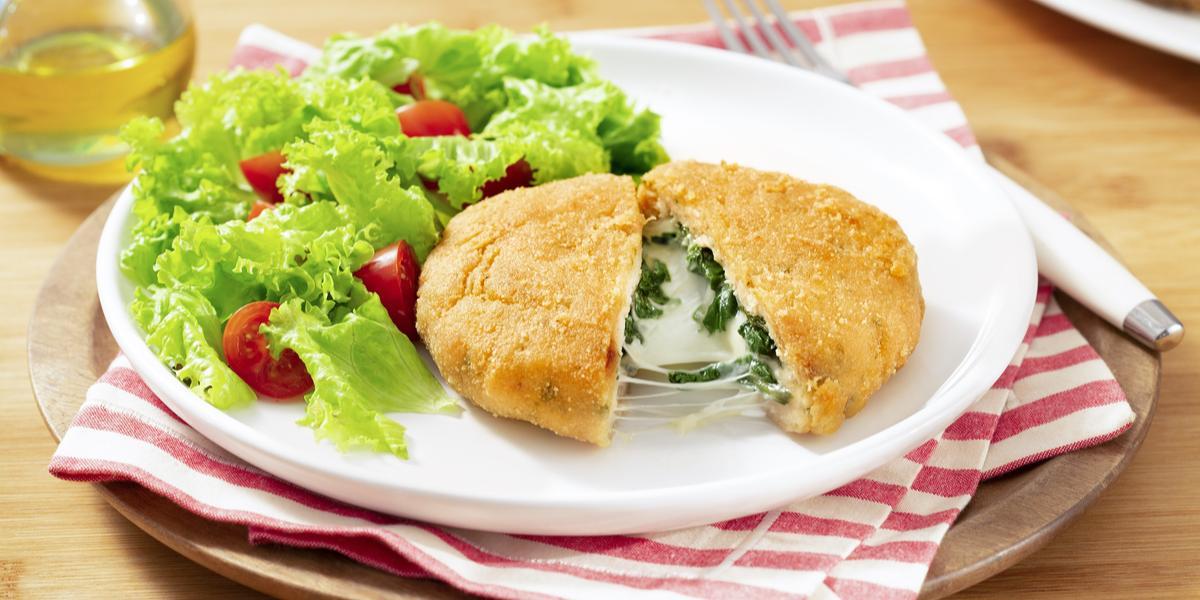 Fotografia em tons de marrom e vermelho de uma bancada marrom um prato redondo marrom, sobre ele um paninho branco e vermelho e um prato branco redondo com o polpetone e uma salda de alface com tomate.