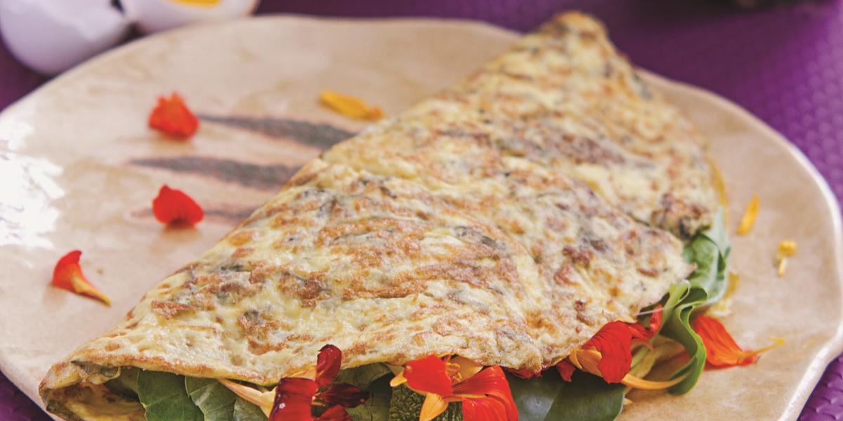 Foto de uma bancada com toalha roxa. Há um prato bege com a receita da omelete com folhas verdes e, ao fundo, dois vasos de plantas e uma cestinha com ovos.