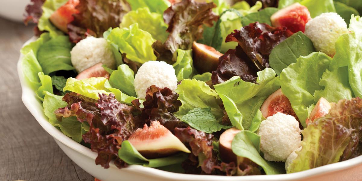 Uma bancada de madeira cinza vista de cima contém um pano laranja, um recipiente redondo e branco com salada dentro pedaços de figo e bolinhas de ricota. À frente duas colheres verdes para mexer a salada.