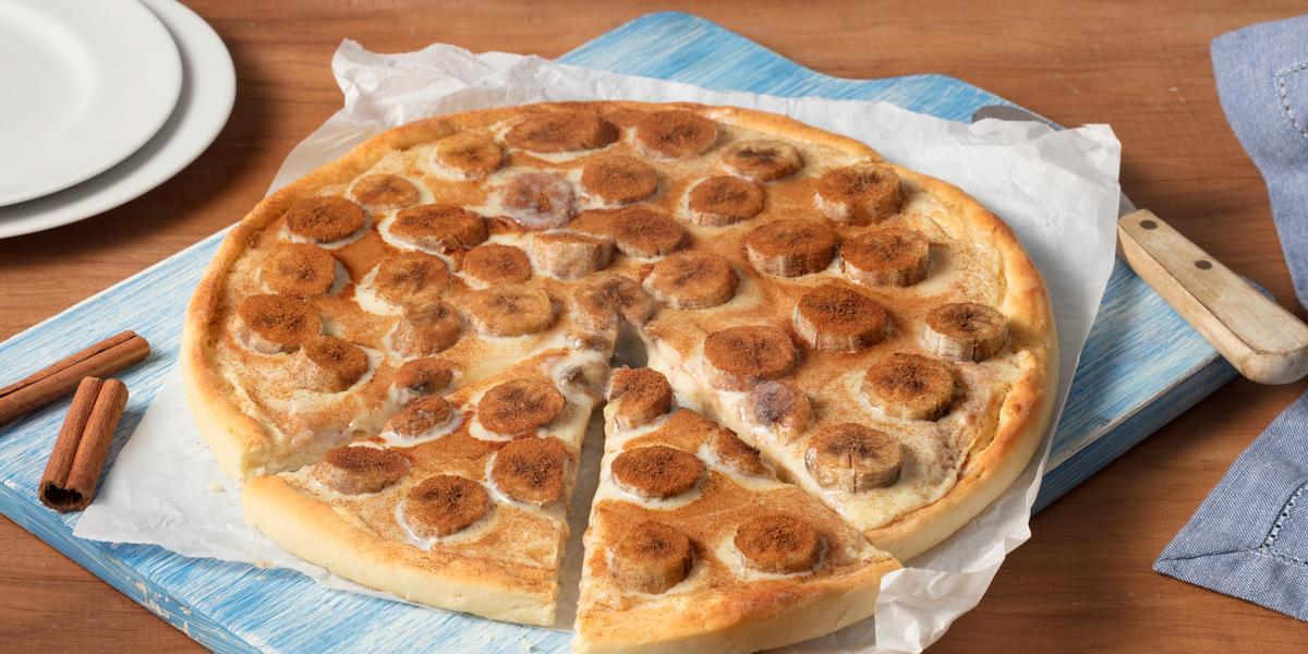 Fotografia em tons de bege e azul, de uma bancada de madeira, ao centro a pizza com rodelas de banana é servida em um papel de seda e uma tábua azul. Ao fundo canela e pratos brancos para decorar.