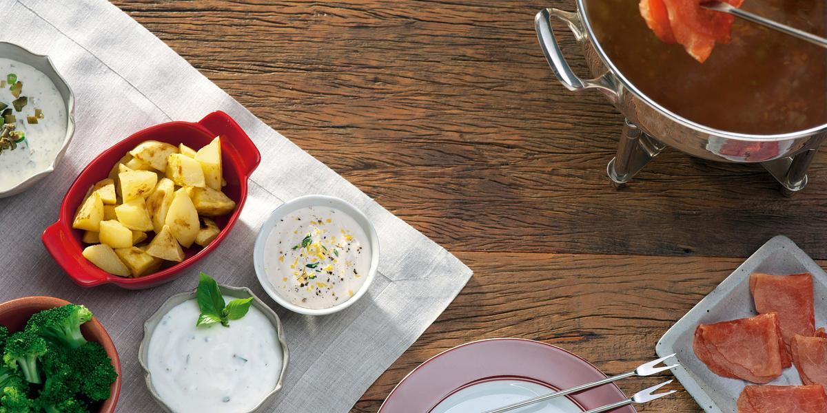 fotografia em tons de marrom e branco de uma bancada vista de cima, contém 3 potes redondos, 2 deles estão com creme e um com brócolis. Um pote vermelho, um prato redondo branco e uma panela de fondue.