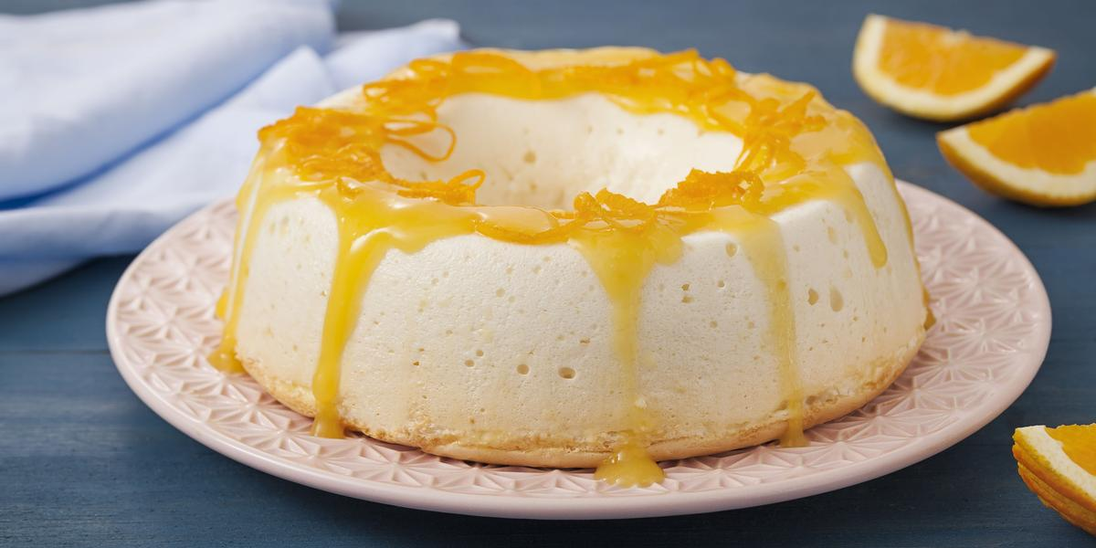 Fotografia em tons de azul e branco de uma bancada azul com um prato rosa, sobre ele um pudim com calda de laranja. Ao lado fatias de laranja e um paninho azul.