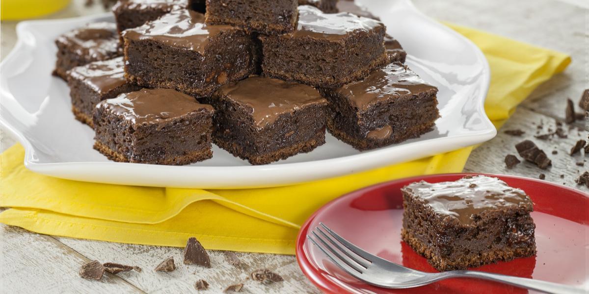 Fotografia em tons de chocolate, branco e amarelo, com prato branco com pedaços de bolo de chocolate sobre guardanapo amarelo, prato vermelho com porção de bolo e um garfo, no alto pote amarelo com chocolate, sobre bancada clara com pedaços de chocolate.