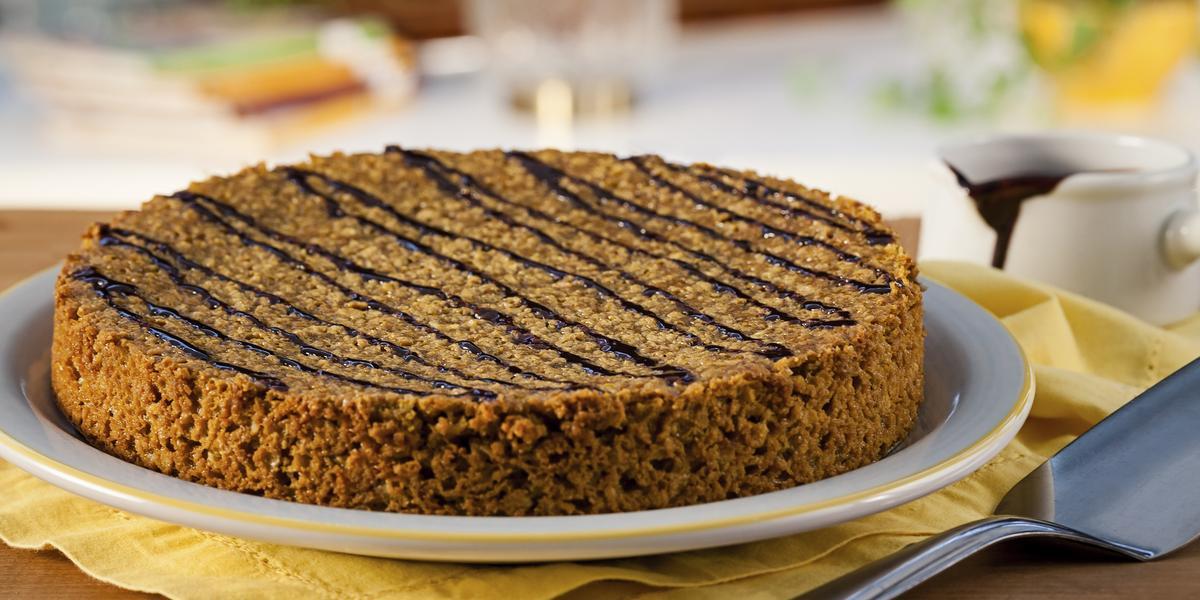 Fotografia em tons de amarelo em uma bancada de madeira com um prato raso branco grande com detalhes em amarelo e o bolo de cenoura em cima dele Ao lado, uma espátula para bolo e uma xícara branca.