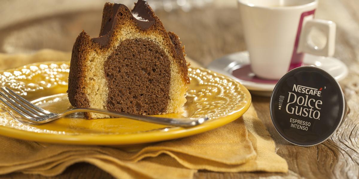 Fotografia em tons de marrom e amarelo de uma bancada de madeira com um paninho amarelo, sobre ele um prato redondo amarelo com uma fatia do bolo e um garfo. Ao fundo uma xícara branca com detalhes vermelhos e uma capsula de Dolce Gusto.