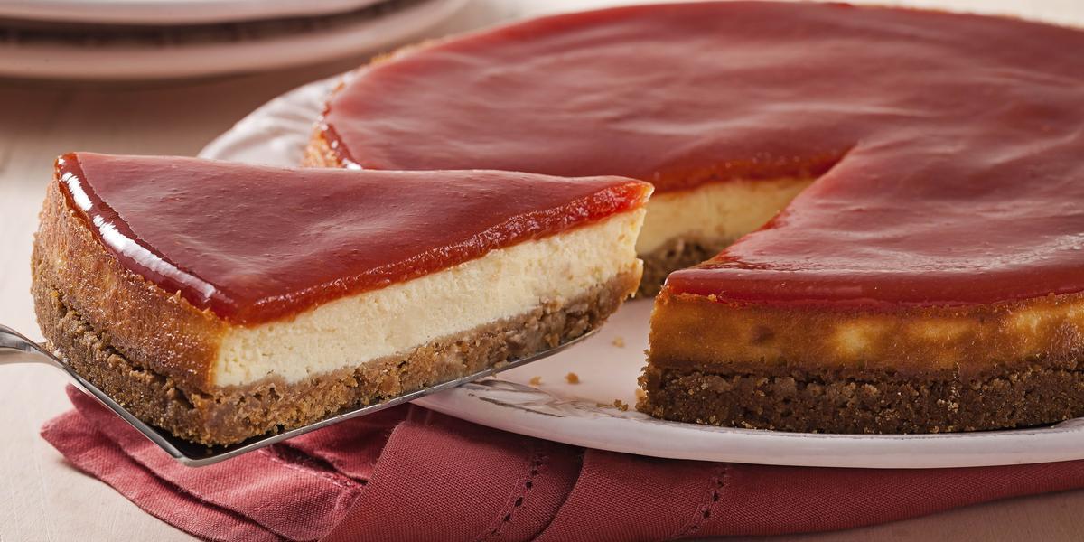 Fotografia em tons de branco e rosa de uma bancada branca com um paninho rosa, sobre ele um prato branco com torta de goiabada. Ao fundo dois pratos brancos.