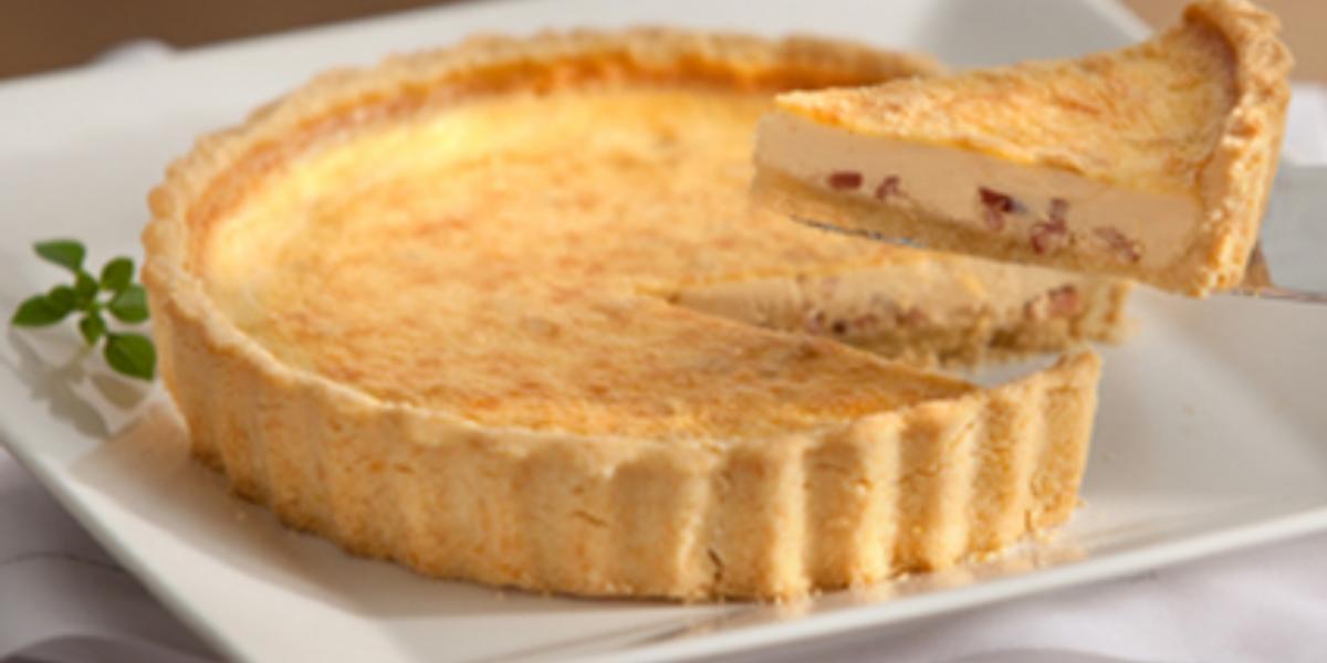 Torta servida em um recipiente retangular cor branco e abaixo um pano branco.