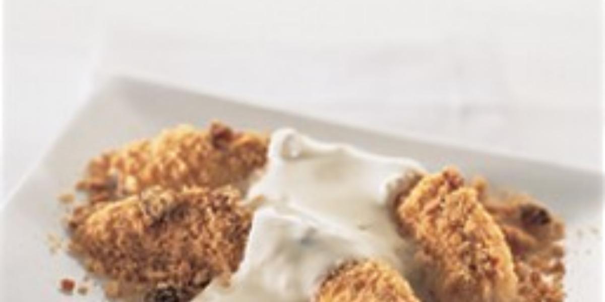 fotografia em tons de branco e marrom tirada de uma prato branco retangular com duas bananas assadas com creme de leite por cima