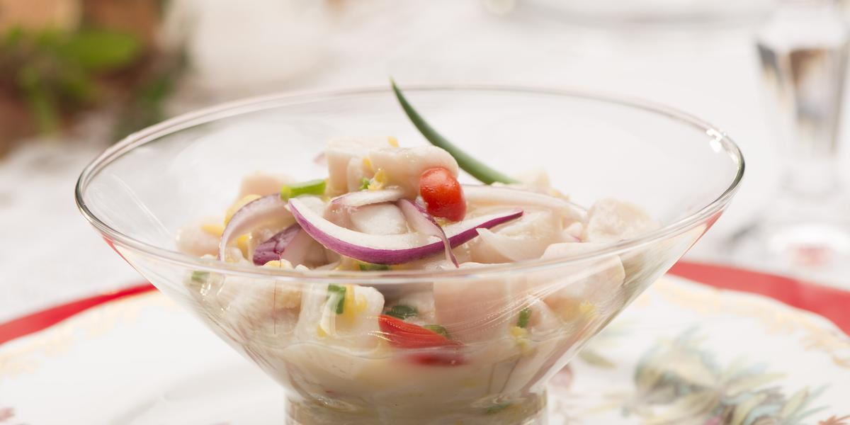 Fotografia em tons de branco e vermelho de uma mesa branca com um prato vermelho, sobre ele um prato branco florido, uma colher prata, e uma taça com pedaços de peixe, cebola roxa, pimenta e cebolinha. Ao fundo um arranjo de flores.