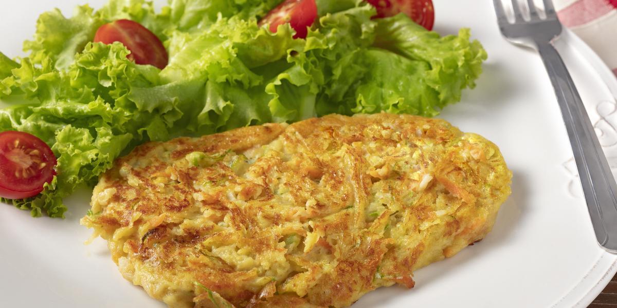Fotografia em tons de branco, verde e amarelo de um prato branco redondo com folhas de alface com tomate, uma tortilha e um garfo sobre o prato. Ao fundo um paninho xadrez vermelho e branco.