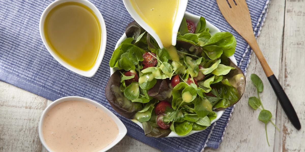 Fotografia em tons de azul, verde e amarelo de uma bancada branca com um paninho azul, sobre ele um prato branco redondo com salada de folhas. Ao redor, três recipiente brancos com molho para salada. Ao lado um garfo para salada.