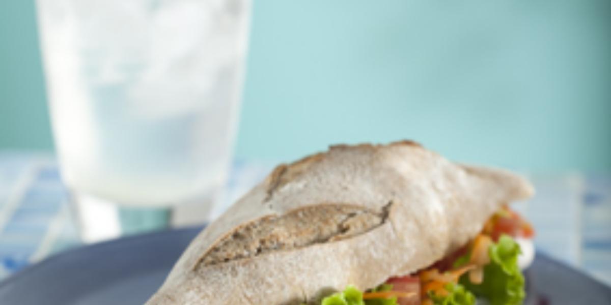 Fotografia em tons de azul e marrom, com prato azul contendo sanduiche recheado com folhas verdes e legumes, ao lado copo com água e gelo, sobre bancada de ladrilhos em tons de azul, e com o fundo azul.