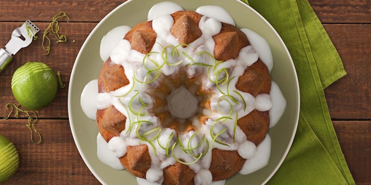 Fotografia em tons de marrom, branco e verde de uma bancada de madeira marrom vista de cima, ao centro um pano verde e por cima um prato branco redondo que contém um bolo com cobertura de iogurte e raspas de limão para decorar.