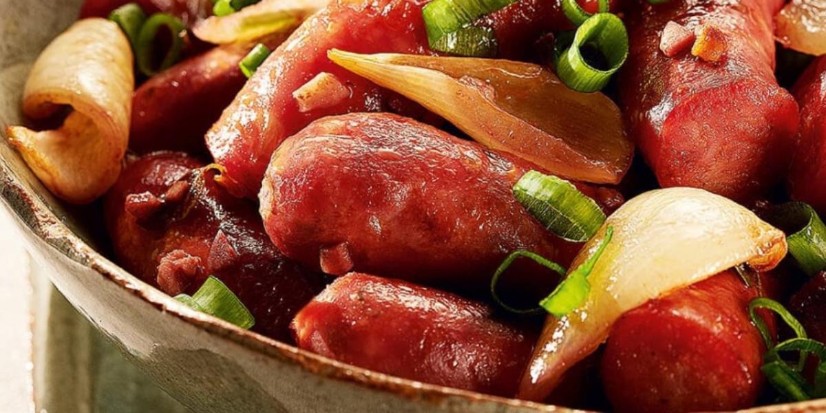 Fotografia em tons de vermelho em um bowl com várias linguiças aceboladas, temperadas com vinho e cebolinha verde.