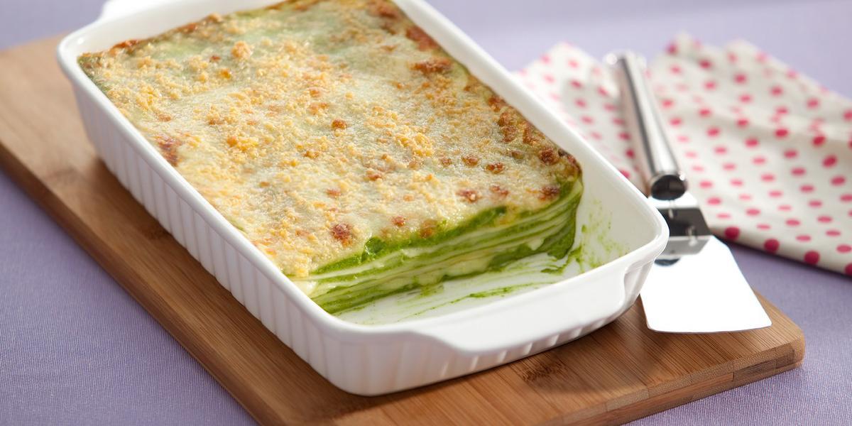 Fotografia em tons de branco e verde, com refratário branco contendo uma lasanha de espinafre gratinada, sobre uma tábua de cozinha com uma espátula de servir sobre um guardanapo branco com bolinhas vermelhas em uma bancada lilás.