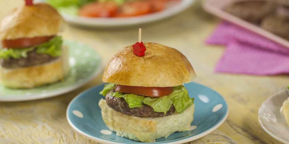 Fotografia em tons de azul e rosa em uma bancada de madeira com um prato pequeno azul com bolinhas brancas no centro com um hambúrguer em cima dele. Ao lado, um prato verde com bolinhas brancas com outro hambúrguer em cima dele.