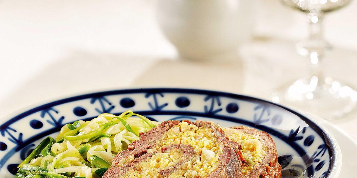 Fotografia em tons de branco, azul verde e amarelo de uma bancada branca vista de cima, contém um prato branco redondo e por coma um prato redondo branco e azul que contém dois rolinhos de carne recheados com farofa. Ao lado um garfo para servir.