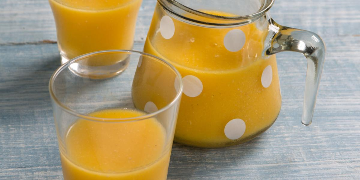 Fotografia em tons de azul e amarelo com uma jarra de vidro com bolinhas brancas e dois copos contendo suco de frutas, tudo sobre bancada em tons de azul.