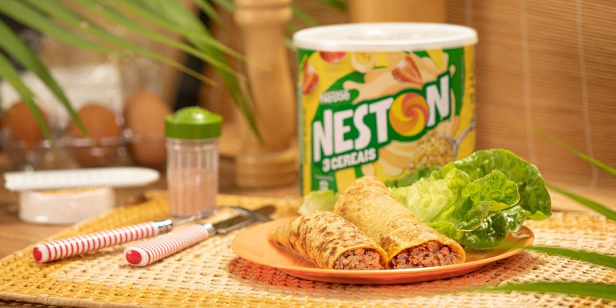 Foto de uma bancada, sobre ela há um jogo americano e nele um prato com dois wraps recheados. Ao fundo há uma lata de Neston 3 Cereais, alguns talheres e outros utensílios. Há algumas plantas compondo a imagem.
