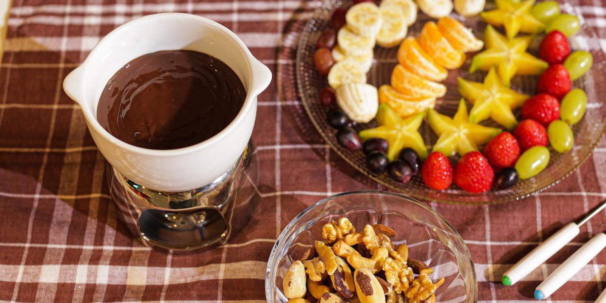 Fotografia em tons de marrom em uma bancada com uma toalha xadrez em marrom, com uma pequena panela branca com o fondue de chocolate dentro, ao fundo um recipiente com frutas picadas e um potinho de vidro com castanhas e amêndoas.
