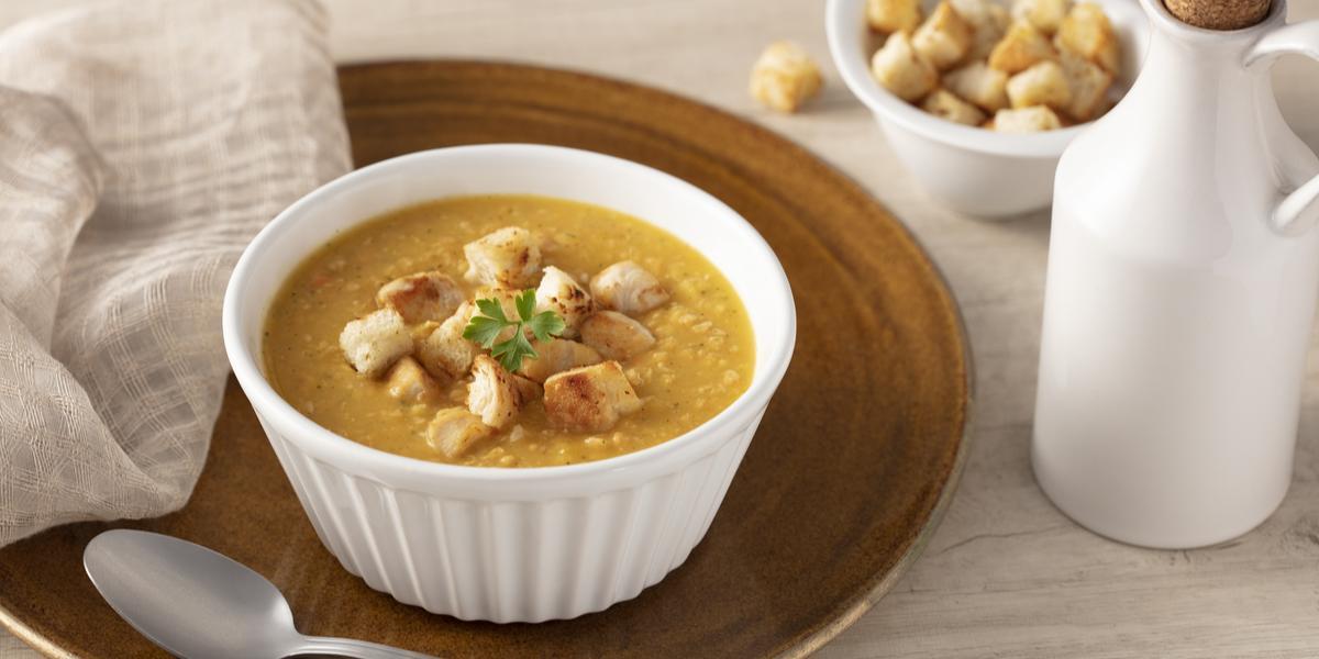 Fotografia em tons de bege de uma bancada, um prato marrom com um potinho branco com a sopa e pequenas torradinhas. Ao lado uma colher prata e do outro lado um pote com pedacinhos de torrada e uma jarra branca.