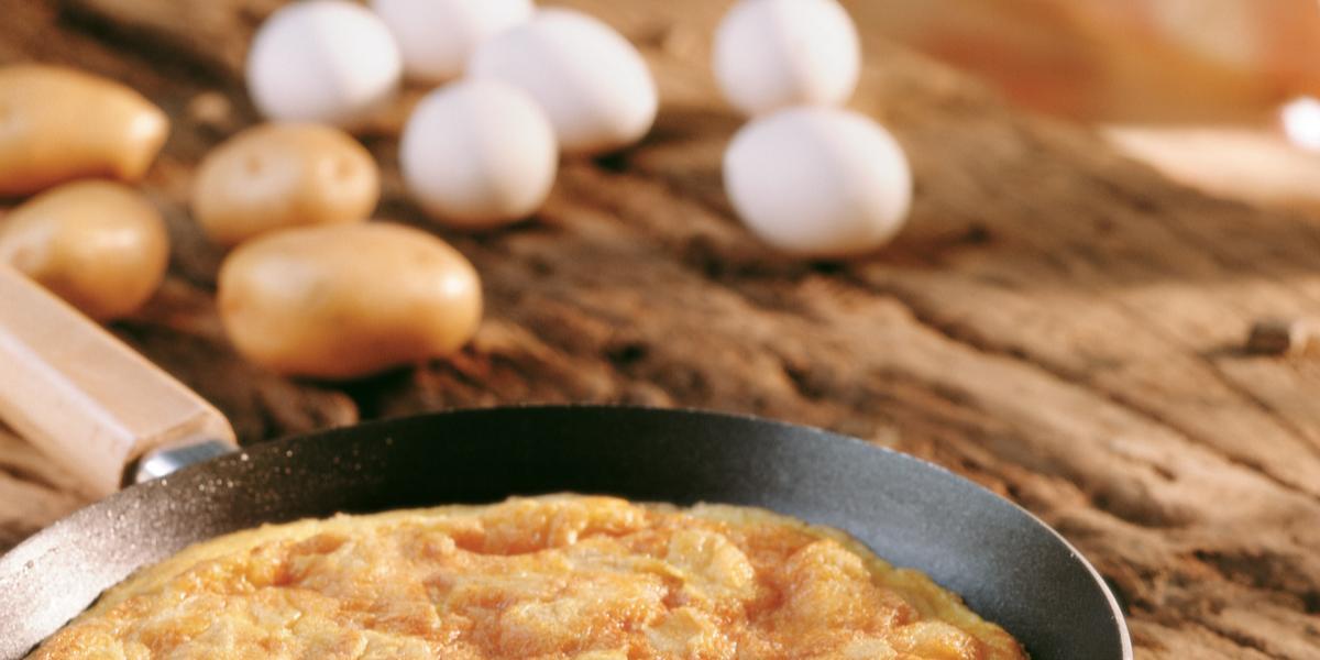 Fotografia em tons de bege em uma bancada de madeira, uma frigideira preta com uma fritada de batata dentro. No fundo da foto existem alguns ovos.