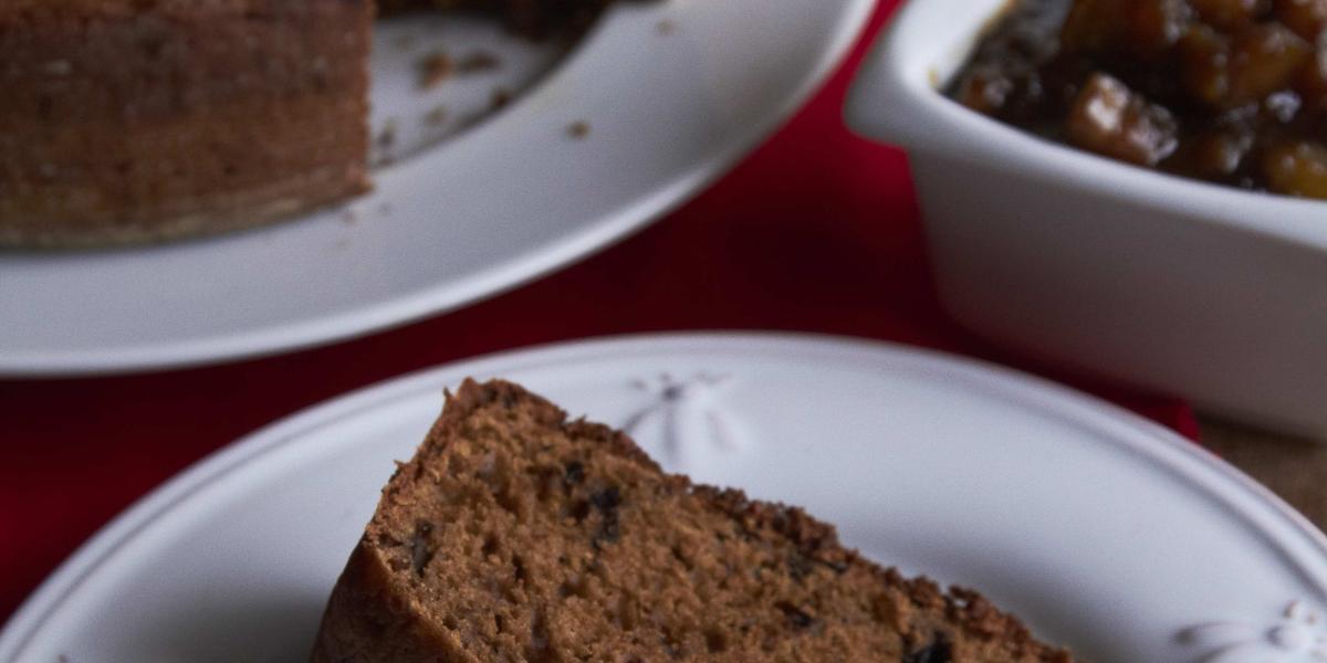 Fotografia em tons de marrom em uma mesa de madeira com um guardanapo vermelho, um prato branco redondo raso com uma fatia de bolo de chocolate com geleia de banana. Ao fundo, um prato maior com o bolo inteiro.