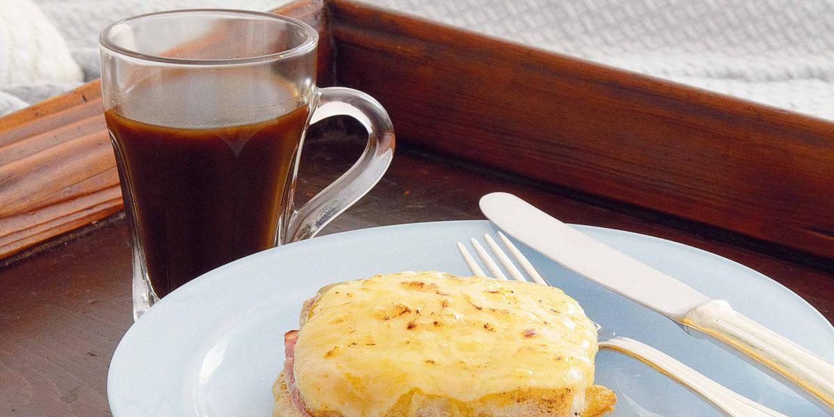 Fotografia em tons de amarela, marrom e rosa de uma bandeja de café da manhã em cima da cama, ao centro um prato branco redondo, dentro dele sanduíche, talheres e uma café preto. Abaixo do prato uma guardanapo azul claro xadrez para decorar.